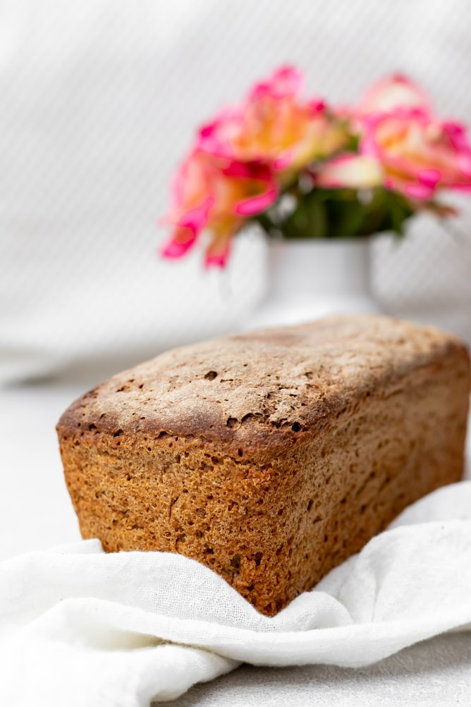 fresh khorasan wheat bread on a white tablecloth with flowers in the background made using Campbell Farm Grains